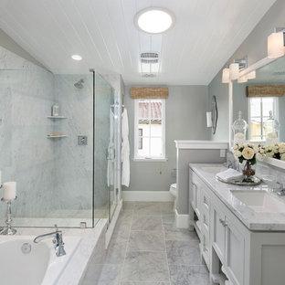Esempio di una stanza da bagno padronale chic con ante con riquadro incassato, ante grigie, vasca da incasso, piastrelle grigie, pareti grigie, lavabo sottopiano e porta doccia a battente
