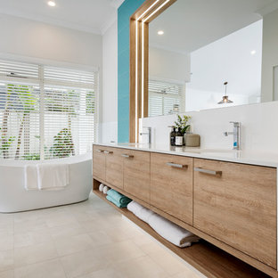 Design ideas for a beach style master bathroom in Perth with flat-panel cabinets, light wood cabinets, a freestanding tub, blue tile, blue walls, a wall-mount sink, white floor and white benchtops.