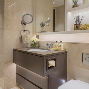 Inspiration for a contemporary bathroom in London with flat-panel cabinets, brown cabinets, a one-piece toilet, beige tiles and a submerged sink.