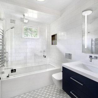 ニューヨークの中くらいのモダンスタイルのおしゃれな浴室 (フラットパネル扉のキャビネット、青いキャビネット、アンダーマウント型浴槽、シャワー付き浴槽、壁掛け式トイレ、白いタイル、大理石タイル、白い壁、モザイクタイル、アンダーカウンター洗面器、大理石の洗面台、グレーの床、開き戸のシャワー、白い洗面カウンター) の写真