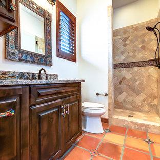 Inredning av ett amerikanskt badrum, med granitbänkskiva, en dubbeldusch, flerfärgad kakel, perrakottakakel och klinkergolv i terrakotta