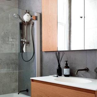 Ejemplo de cuarto de baño actual con armarios con paneles lisos, puertas de armario de madera oscura, bañera empotrada, combinación de ducha y bañera, baldosas y/o azulejos grises, lavabo integrado, suelo gris y encimeras blancas