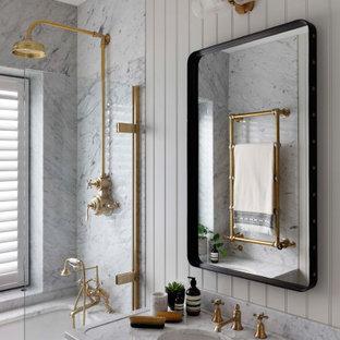 Идея дизайна: ванная комната среднего размера в стиле современная классика с полновстраиваемой ванной, душем над ванной, серой плиткой, серыми стенами, душевой кабиной, консольной раковиной, серой столешницей и панелями на части стены