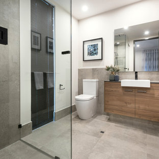 This is an example of a contemporary 3/4 bathroom in Perth with flat-panel cabinets, medium wood cabinets, a corner shower, gray tile, white walls, a drop-in sink, grey floor and a hinged shower door.