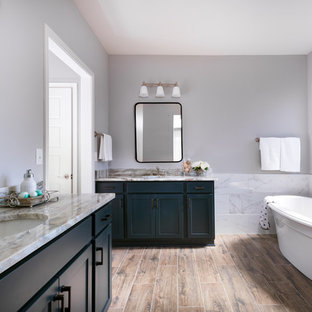 Elegant white tile medium tone wood floor and brown floor freestanding bathtub photo in Other with shaker cabinets, blue cabinets, gray walls, an undermount sink and beige countertops