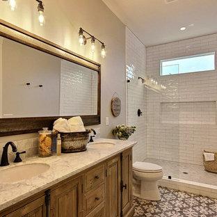 Пример оригинального дизайна: огромная ванная комната в стиле кантри с фасадами в стиле шейкер, искусственно-состаренными фасадами, душем в нише, унитазом-моноблоком, белой плиткой, керамогранитной плиткой, бежевыми стенами, полом из керамической плитки, душевой кабиной, врезной раковиной, столешницей из искусственного кварца, разноцветным полом, открытым душем и серой столешницей