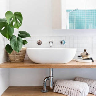 This is an example of a beach style bathroom in Wollongong with open cabinets, medium wood cabinets, blue tile, mosaic tile, white walls, a vessel sink, wood benchtops and brown benchtops.
