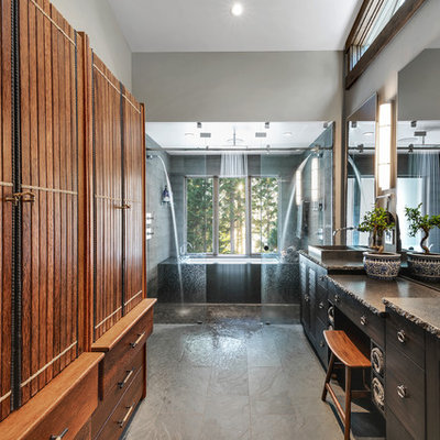 Example of a large mountain style master gray tile and stone tile ceramic tile and gray floor bathroom design in Other with furniture-like cabinets, brown cabinets, an undermount tub, a one-piece toilet, gray walls, a vessel sink, granite countertops and gray countertops