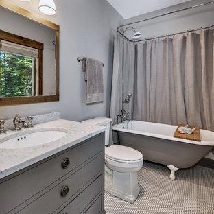 Ejemplo de cuarto de baño infantil, rústico, pequeño, con armarios tipo mueble, puertas de armario grises, bañera con patas, combinación de ducha y bañera, sanitario de una pieza, baldosas y/o azulejos grises, paredes grises, suelo con mosaicos de baldosas, lavabo bajoencimera, encimera de granito, suelo blanco, ducha con cortina y encimeras grises