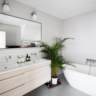 Photo of a medium sized contemporary family bathroom in London with flat-panel cabinets, light wood cabinets, a freestanding bath, white tiles, porcelain tiles, white walls, ceramic flooring, a built-in sink, solid surface worktops and grey floors.