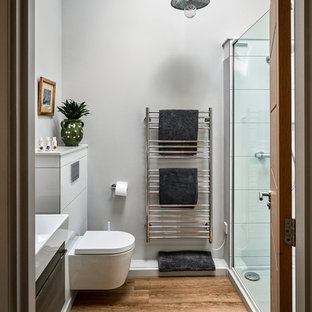 Small rural ensuite bathroom in Surrey with flat-panel cabinets, grey cabinets, a corner shower, a wall mounted toilet, grey walls, a console sink, brown floors and a hinged door.