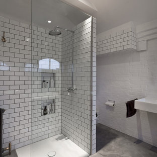 Inspiration for a contemporary bathroom in London with white tiles, metro tiles, a built-in shower, a wall-mounted sink, white walls and concrete flooring.