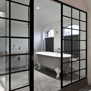 Inspiration for a contemporary concrete floor claw-foot bathtub remodel in London with a wall-mount sink and white walls