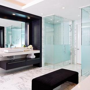 Foto på ett mycket stort funkis vit en-suite badrum, med ett fristående handfat, släta luckor, svarta skåp, en hörndusch, vit kakel, marmorkakel, vita väggar, marmorgolv, bänkskiva i akrylsten, vitt golv och dusch med gångjärnsdörr