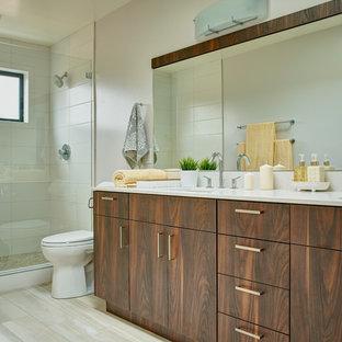 Esempio di una grande stanza da bagno padronale design con ante lisce, ante in legno scuro, doccia alcova, WC a due pezzi, piastrelle bianche, piastrelle in ceramica, pareti bianche, pavimento in compensato, lavabo sottopiano e top in superficie solida