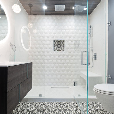 Trendy 3/4 white tile multicolored floor alcove shower photo in San Francisco with flat-panel cabinets, dark wood cabinets, a wall-mount toilet, gray walls, an integrated sink, a hinged shower door and white countertops