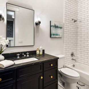 Inredning av ett klassiskt svart svart badrum med dusch, med luckor med infälld panel, svarta skåp, ett badkar i en alkov, en dusch/badkar-kombination, en toalettstol med separat cisternkåpa, vit kakel, tunnelbanekakel, vita väggar, mosaikgolv, ett undermonterad handfat och flerfärgat golv