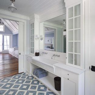 Modelo de cuarto de baño infantil, campestre, con armarios con paneles empotrados, puertas de armario blancas, paredes azules, lavabo de seno grande y suelo azul