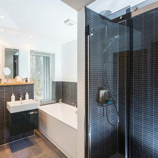 Пример оригинального дизайна: главная ванная комната среднего размера в современном стиле с плоскими фасадами, серыми фасадами, угловой ванной, душем в нише, инсталляцией, белыми стенами, столешницей из дерева, серым полом, душем с раздвижными дверями, удлиненной плиткой, черной плиткой, монолитной раковиной и белой столешницей