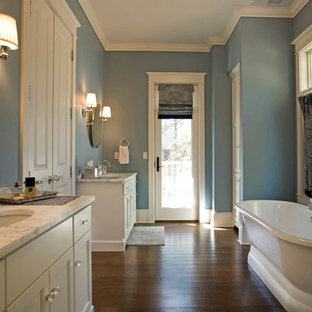 Photo of a large traditional master bathroom in Milwaukee with a freestanding tub, recessed-panel cabinets, white cabinets, blue walls, medium hardwood floors, an undermount sink, quartzite benchtops and brown floor.