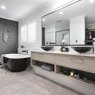 Inspiration for a contemporary master bathroom in Perth with flat-panel cabinets, brown cabinets, a freestanding tub, an alcove shower, gray tile, white walls, a vessel sink, beige floor and a hinged shower door.