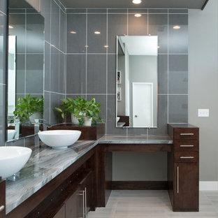 Foto på ett stort funkis en-suite badrum, med släta luckor, skåp i mörkt trä, ett fristående badkar, en hörndusch, en toalettstol med separat cisternkåpa, blå kakel, grå kakel, glaskakel, grå väggar, laminatgolv, ett fristående handfat, granitbänkskiva, beiget golv och dusch med gångjärnsdörr