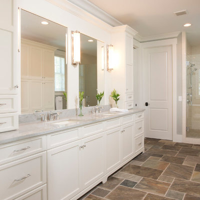 Inspiration for a large timeless master porcelain tile and brown floor alcove shower remodel in Charleston with an undermount sink, recessed-panel cabinets, white cabinets, gray walls, granite countertops, a two-piece toilet, a hinged shower door and gray countertops