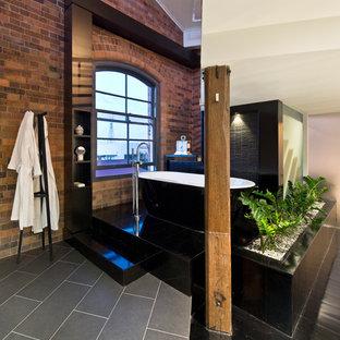 Esempio di una stanza da bagno industriale di medie dimensioni con vasca freestanding, piastrelle nere e pavimento nero