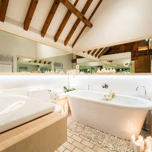 Idee per una stanza da bagno minimal con lavabo da incasso, ante in legno chiaro, vasca freestanding, pareti bianche e pavimento in mattoni