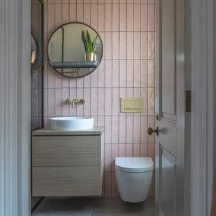 Bild på ett funkis beige beige badrum, med släta luckor, skåp i ljust trä, rosa kakel, ett fristående handfat, träbänkskiva och grått golv