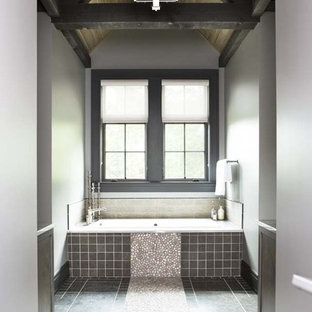 Example of a large mountain style master gray tile and pebble tile pebble tile floor alcove bathtub design in Other with gray walls