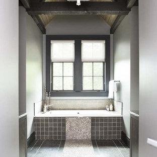 Esempio di una grande stanza da bagno padronale stile rurale con piastrelle grigie, piastrelle di ciottoli, pavimento con piastrelle di ciottoli, vasca ad alcova e pareti grigie