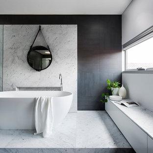 Новые идеи обустройства дома: большая главная ванная комната в современном стиле с отдельно стоящей ванной, открытым душем, серой плиткой, плиткой из листового камня, серыми стенами, мраморным полом и столешницей из искусственного камня