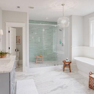 Ejemplo de cuarto de baño principal, tradicional renovado, con puertas de armario grises, bañera exenta, baldosas y/o azulejos verdes, paredes grises, suelo de mármol y suelo gris