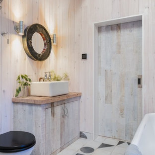 Design ideas for a rustic shower room bathroom in Cornwall with light wood cabinets, a freestanding bath, a two-piece toilet, beige walls, ceramic flooring, a vessel sink, wooden worktops, multi-coloured floors, flat-panel cabinets and brown worktops.