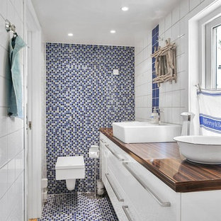 Inspiration for a medium sized nautical bathroom in Stockholm with a vessel sink, flat-panel cabinets, white cabinets, a wall mounted toilet, blue tiles, mosaic tiles and mosaic tile flooring.