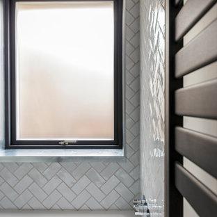 Foto de cuarto de baño infantil, contemporáneo, de tamaño medio, con bañera encastrada, ducha abierta, sanitario de pared, baldosas y/o azulejos grises, baldosas y/o azulejos de cerámica, paredes blancas, suelo de cemento y lavabo suspendido