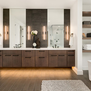 Large contemporary ensuite bathroom in Seattle with flat-panel cabinets, a freestanding bath, white walls, a submerged sink, engineered stone worktops, white worktops, brown cabinets and brown floors.