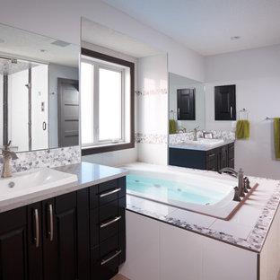 Großes Modernes Badezimmer En Suite mit Einbaubadewanne, weißer Wandfarbe, flächenbündigen Schrankfronten, schwarzen Schränken, Duschnische, schwarz-weißen Fliesen, grauen Fliesen, Kieselfliesen, Porzellan-Bodenfliesen, Unterbauwaschbecken und Granit-Waschbecken/Waschtisch in Calgary
