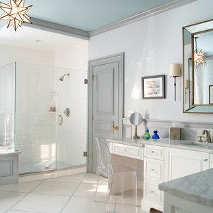 ニューヨークの中くらいのトランジショナルスタイルのおしゃれなマスターバスルーム (アンダーカウンター洗面器、白いキャビネット、ドロップイン型浴槽、コーナー設置型シャワー、白いタイル、サブウェイタイル、グレーの壁、インセット扉のキャビネット、磁器タイルの床、ベージュの床、開き戸のシャワー、ビデ、大理石の洗面台) の写真