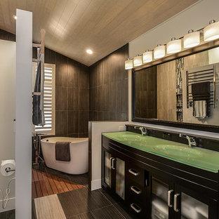 Inredning av ett modernt litet en-suite badrum, med ett integrerad handfat, möbel-liknande, skåp i mörkt trä, bänkskiva i glas, ett fristående badkar, en hörndusch, en toalettstol med hel cisternkåpa, grå kakel och vita väggar