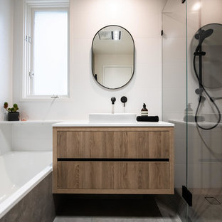 Design ideas for a mid-sized contemporary master bathroom in Melbourne with furniture-like cabinets, medium wood cabinets, a corner shower, white tile, ceramic tile, white walls, porcelain floors, a vessel sink, engineered quartz benchtops, brown floor, a hinged shower door and white benchtops.