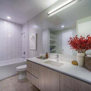 ロサンゼルスのモダンスタイルのおしゃれな浴室 (オーバーカウンターシンク、フラットパネル扉のキャビネット、茶色いキャビネット、珪岩の洗面台、大型浴槽、オープン型シャワー、一体型トイレ、白いタイル、磁器タイル、白い壁、コンクリートの床) の写真