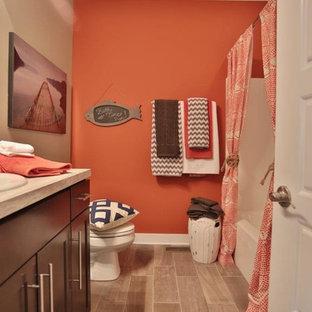 Modelo de cuarto de baño infantil, clásico renovado, pequeño, con lavabo bajoencimera, armarios estilo shaker, puertas de armario de madera en tonos medios, encimera de laminado, combinación de ducha y bañera, sanitario de una pieza, baldosas y/o azulejos grises, baldosas y/o azulejos de cerámica, paredes grises, suelo de baldosas de cerámica y bañera encastrada