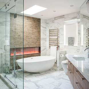 Design ideas for a large contemporary master bathroom in Vancouver with flat-panel cabinets, medium wood cabinets, a freestanding tub, white tile, an undermount sink, white floor, a corner shower, a one-piece toilet, marble, white walls, marble floors, marble benchtops, a hinged shower door and white benchtops.