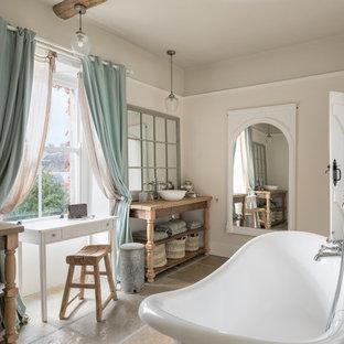 Modelo de cuarto de baño romántico con armarios abiertos, bañera exenta, paredes beige, lavabo sobreencimera, encimera de madera, suelo marrón y encimeras marrones