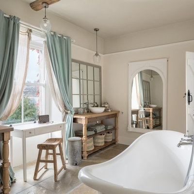Inspiration for a shabby-chic style brown floor freestanding bathtub remodel in Gloucestershire with open cabinets, beige walls, a vessel sink, wood countertops and brown countertops
