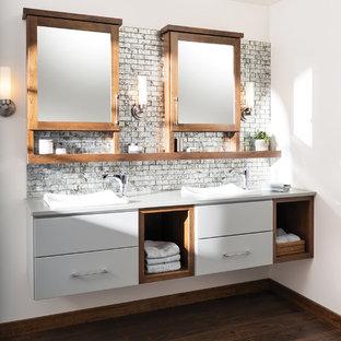 На фото: ванная комната в современном стиле с накладной раковиной, серыми фасадами, столешницей из искусственного камня, серой плиткой, стеклянной плиткой, белыми стенами и темным паркетным полом