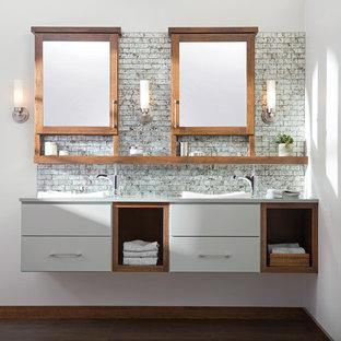 Foto di una stanza da bagno design con lavabo da incasso, ante grigie, top in superficie solida, piastrelle grigie, piastrelle di vetro, pareti bianche e parquet scuro