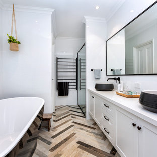 Photo of a mid-sized beach style master bathroom in Perth with shaker cabinets, white cabinets, a freestanding tub, a corner shower, a two-piece toilet, white tile, ceramic tile, white walls, mosaic tile floors, a vessel sink, engineered quartz benchtops, brown floor, a hinged shower door, white benchtops, a double vanity and a built-in vanity.